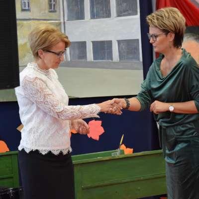 Anna Dziewior przekazuje gratulacje dyrektor szkoły, uścisk dłoni obu pań, przechylenie głowy w geście szacunku
