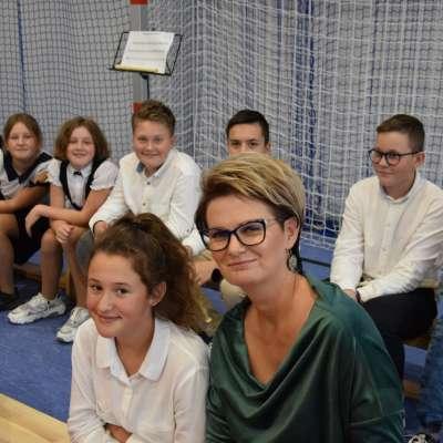 Zdjęcie przedstawia Anne Dziewior wraz z uczniami ubranymi w białe koszule, wszyscy na zdjęciu są uśmiechnięci