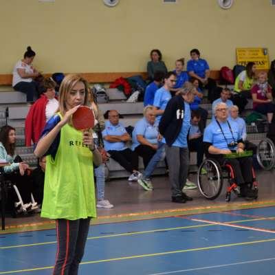 Dziewczyna w zielonej odblaskowej koszulce trzyma uniesioną czerwoną paletkę do tenisa stołowego sygnalizując rzeczy związane z rozgrywką boccia zawodnikom siedzącym na wózkach