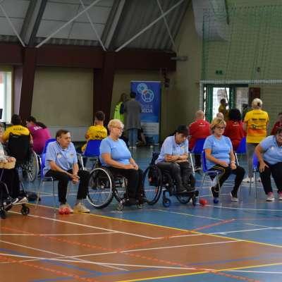 Zdjęcie przedstawia ogólny rzut na salę sportową gdzie osoby siedzące na wózkach inwalidzkich rozgrywają zawody Boccia